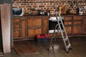 Fotografie interior of loft style kitchen with stepladder, toolbox and laminate planks on floor