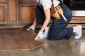cropped shot of repairwoman installing laminate onto kitchen floor