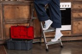 Fotografie cropped shot of repairwoman standing on stepladder at kitchen