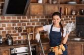 Lächelnde junge Reparaturfrau mit Leiter und Schraubenschlüssel steht in der Küche