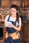 Photo serious young repairwoman with toolbelt using tablet at kitchen