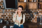beautiful young woman talking by phone at kitchen