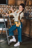 Fotografie beautiful young repairwoman standing on stepladder and examining light bulb at kitchen