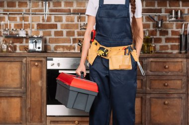 cropped shot of repairwoman with toolbox and toolbelt standing at kitchen