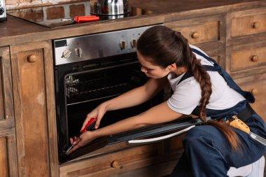 young repairwoman repairing oven with screwdriver