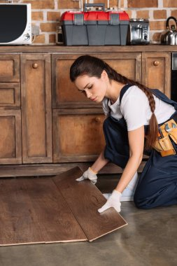 serious young repairwoman installing laminate onto kitchen floor