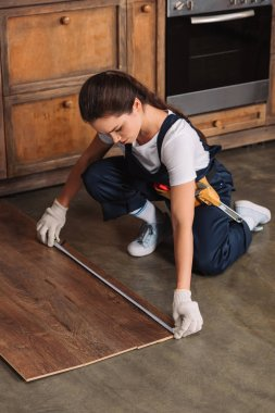 beautiful young repairwoman with measuring tape installing laminate onto kitchen floor