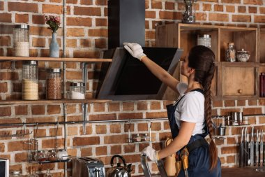 young repairwoman in overall touching stove hood at kitchen