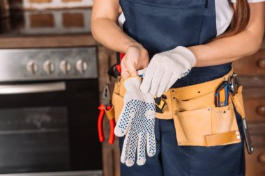 Cropped shot of repairwoman putting on work gloves at kitchen stock vector