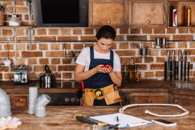 attractive young female plumber using smartphone at kitchen