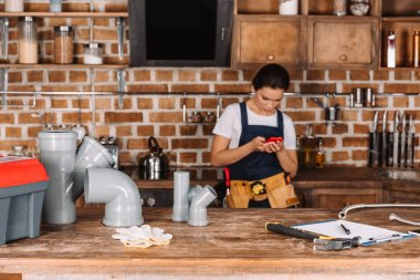 beautiful young female plumber using smartphone at kitchen