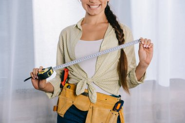 Cropped shot of smiling young repairwoman with measuring tape stock vector