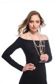 Fotografia donna sicura elegante in vestito nero che tiene il bicchiere di champagne isolato su priorità bassa bianca