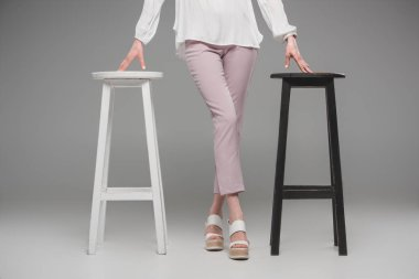 cropped image of female model standing between chairs on grey background