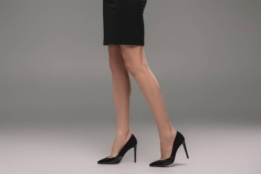 cropped image of businesswoman in shoes with high heels on grey background