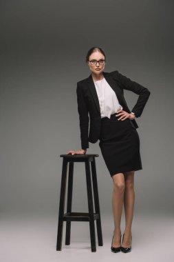 beautiful businesswoman in eyeglasses posing near chair on grey background