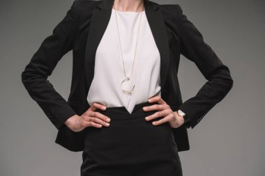 cropped image of businesswoman standing with hands on hips isolated on grey background