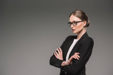 serious businesswoman in eyeglasses standing with crossed arms isolated on grey background