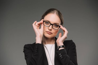 attractive businesswoman adjusting eyeglasses and looking at camera isolated on grey background