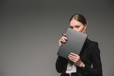 businesswoman covering face by textbook isolated on grey background