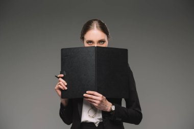 serious businesswoman covering face by textbook and looking at camera isolated on grey background
