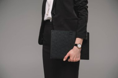 cropped image of businesswoman with wristwatch holding textbook isolated on grey background