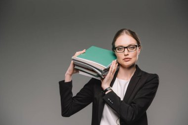 female teacher in eyeglasses holding stack of textbooks isolated on grey background