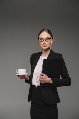 serious businesswoman in eyeglasses holding cup of coffee and textbook isolated on grey background
