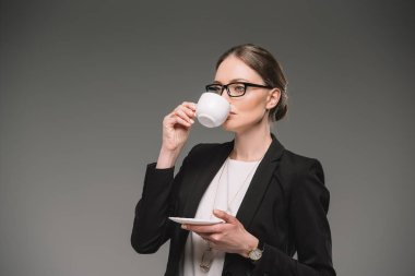 businesswoman in eyeglasses drinking coffee from cup isolated on grey background