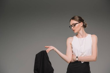 side view of attractive businesswoman in eyeglasses looking away and holding jacket isolated on grey background