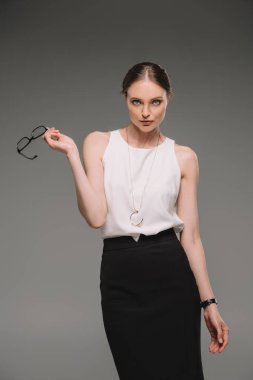 attractive businesswoman holding eyeglasses and looking at camera isolated on grey background
