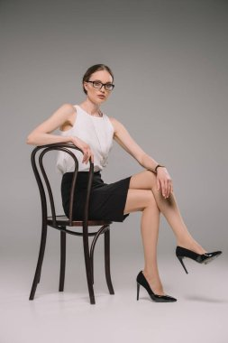 attractive businesswoman in eyeglasses sitting on chair and looking at camera on grey background