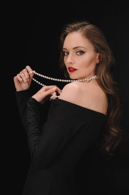 elegant woman in black dress holding beads isolated on black background