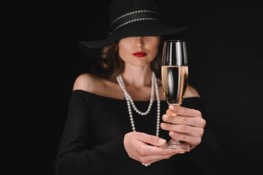 selective focus of champagne glass in hands of elegant woman with covered eyes by straw isolated on black background