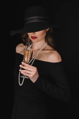 elegant woman with eyes covered by black straw holding champagne glass isolated on black background