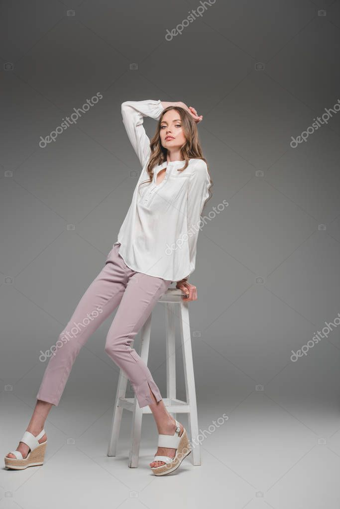 Beautiful woman sitting on chair and looking at camera on grey background stock vector