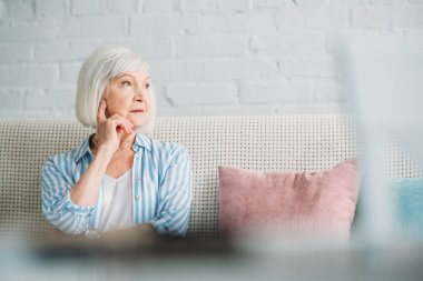 portrait of pensive grey hair woman looking away resting on sofa at home