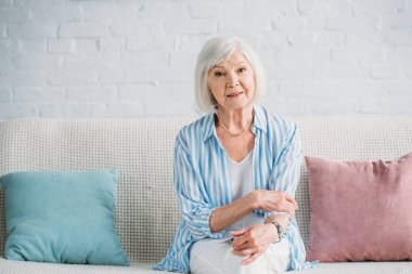 portrait of beautiful grey hair woman resting on sofa at home