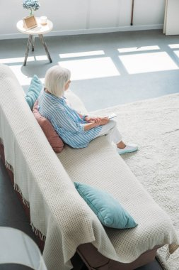 high angle view of senior woman with remote control watching tv on sofa at home