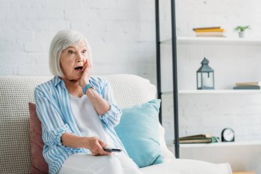 portrait of shocked senior woman with remote control watching tv on sofa at home