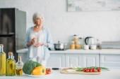 Fotografia fuoco selettivo di verdure fresche sul bancone e senior donna con bicchiere di vino in piedi alla stufa in cucina
