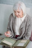 senior lady looking at photos from photo album while resting on couch at home