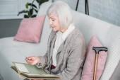 boční pohled na starší lady s fotoalbum na gauči doma
