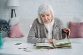 Fotografie portrait  of grey hair woman looking at photos in photo album at table at home