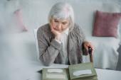 portrét šedivé vlasy ženy při pohledu na fotky ve fotoalbu na stole doma
