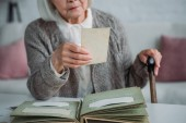 Fotografie partial view of senior woman looking at photo from photo album at table at home