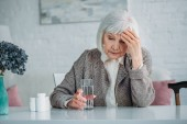 portrait of grey hair woman with headache sitting at table with pills and glass of water at home