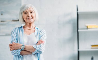 portrait of beautiful smiling senior lady in stylish clothing with arms crossed looking at camera at home