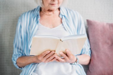 cropped shot of senior woman reading book while resting on sofa at home