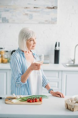 pensive senior lady with glass of wine standing at counter with fresh vegetables on cutting board in kitchen